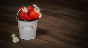 草莓和翠菊在桶 免版税库存照片