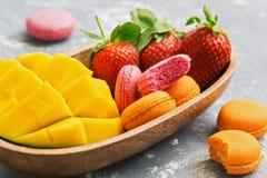 草莓和芒果蛋白杏仁饼干 桃红色和黄色蛋白杏仁饼干用新鲜的草莓和芒果在一个木碗 选择聚焦 免版税库存照片