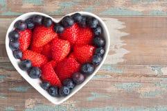 草莓和蓝莓在一个心形的碗 免版税库存图片