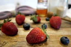 草莓和蓝莓木表面上 库存照片
