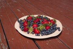 草莓和蓝莓盛肉盘在土气木表上 库存图片