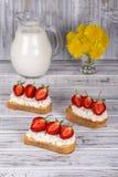 草莓和酸奶干酪三明治在木桌上 库存图片