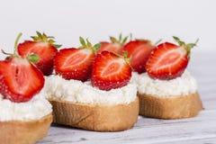 草莓和酸奶干酪三明治在木桌上 免版税库存照片
