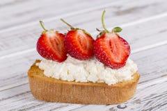 草莓和酸奶干酪三明治在木桌上 库存照片