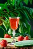 草莓和黄瓜利口酒,在绿色背景 库存照片
