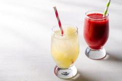 草莓圆滑的人和冰柠檬水与鸡尾酒管在玻璃,在白色背景 免版税库存照片