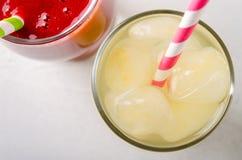 草莓圆滑的人和冰柠檬水与鸡尾酒管在玻璃,在白色背景 免版税图库摄影