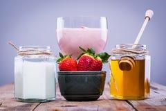 草莓圆滑的人用在旁边新鲜的草莓、蜂蜜和酸奶 免版税库存图片