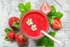草莓圆滑的人顶视图在一块玻璃的与秸杆、花和新鲜的莓果 免版税库存照片