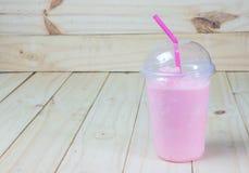草莓在塑料玻璃的圆滑的人酸奶在木背景 图库摄影