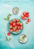 草莓在有薄荷叶的蓝色碗服务并且搽粉了在破旧的别致的木背景的糖 库存图片