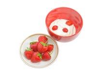 草莓在茶碟和在有打好的奶油的红色碗 免版税库存图片