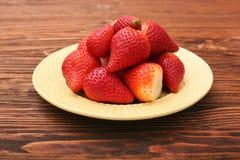 草莓板材在木背景的 免版税库存照片