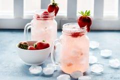 草莓柠檬水用在玻璃的新鲜的草莓柠檬水刺激杯子在碗水平的照片的熔化冰块新鲜的草莓 免版税库存图片
