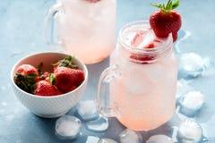 草莓柠檬水用在玻璃的新鲜的草莓柠檬水刺激杯子在碗水平的照片的熔化冰块新鲜的草莓 库存图片
