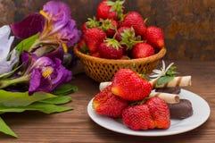草莓用在花背景的巧克力  木的表 特写镜头 图库摄影