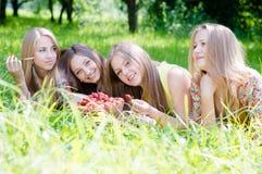 草莓的时刻:4年轻美丽的浅黑肤色的男人&白肤金发的少妇女朋友饮用乐趣被收获的草莓在夏天 库存照片