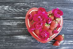 草莓盘心脏,在色的木背景的花玫瑰色夏天招呼的欢乐设计点心 免版税库存图片