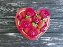 草莓盘心脏,花玫瑰色夏天庆祝招呼在色的木背景的欢乐设计点心 库存图片