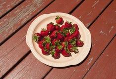 草莓盛肉盘在土气木表上的 库存照片