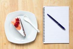 草莓蛋糕和笔记本与笔在木背景 免版税库存图片