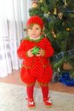 草莓衣服的一岁的女孩在一棵新年树附近站立 免版税库存照片
