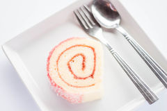 草莓酱与匙子和叉子的卷蛋糕 免版税库存照片