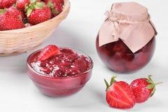 草莓酱在碗和在一个草莓旁边的一个瓶子在白色木背景 免版税库存图片