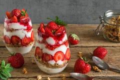 草莓酸奶冷甜点用在玻璃的格兰诺拉麦片,薄荷和新鲜的莓果与在土气木桌上的匙子 图库摄影