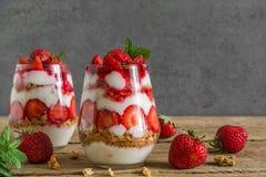 草莓酸奶冷甜点用在玻璃的格兰诺拉麦片,薄荷和新鲜的莓果在土气木桌上 健康的早餐 库存照片