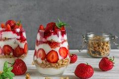 草莓酸奶冷甜点用在玻璃的格兰诺拉麦片,薄荷和新鲜的莓果在白色木桌上 健康的早餐 库存照片