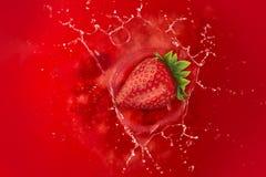 草莓飞溅到汁液里 免版税库存照片