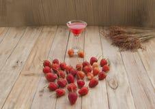草莓,新鲜的莓果在木地板和饮料上安排了 免版税库存照片