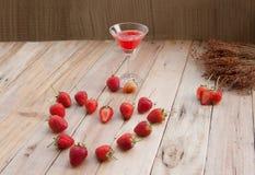 草莓,新鲜的莓果在木地板和饮料上安排了 库存照片