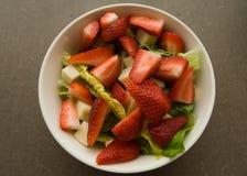 草莓,无盐干酪,在白色碗的莴苣沙拉 库存图片