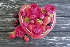 草莓,樱桃,蓝莓自然果子板材心脏,新鲜的葡萄酒开胃花在黑木背景上升了 库存照片