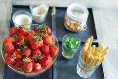 草莓,蜡烛,薄菏,在桌上的面包条 免版税图库摄影