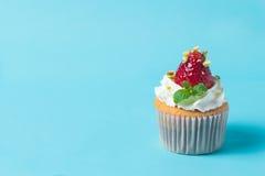 草莓cupcak顶部用开心果和奶油,有选择性的foc 图库摄影