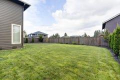 草被填装的后院 布朗房屋板壁房子外部 免版税库存图片