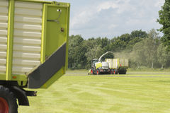 草饲料收获机和运输与拖拉机和loade的 免版税库存照片