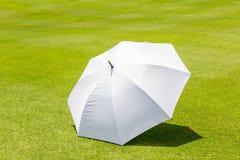 绿草高尔夫球场的白色阳伞地方使用fo 免版税图库摄影