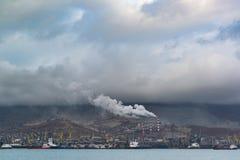 荒凉的工业风景报道以城市和多云天空的烟雾 库存照片