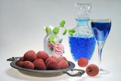 荔枝果子用在玻璃水瓶的蓝色利口酒 图库摄影