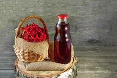 荚莲属的植物莓果在一个篮子的在玻璃透明瓶的一块餐巾汁液旁边 土气 复制空间 免版税库存照片