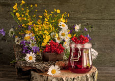 从荚莲属的植物莓果的汁液在玻璃容器的在野花旁边花束的一块餐巾在一个木立场的 土气 库存图片