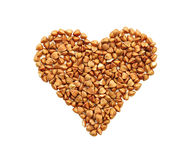 荞麦五谷以心脏的形式在白色背景 免版税图库摄影
