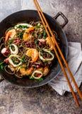 荞麦混乱油炸物面条用海鲜-虾,章鱼,在生铁亚洲铁锅的乌贼有烹调的筷子 顶层 免版税库存图片