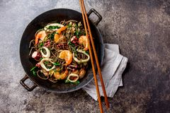 荞麦混乱油炸物面条用海鲜-虾,章鱼,在生铁亚洲铁锅的乌贼有烹调的筷子 顶层 免版税库存照片