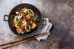 荞麦混乱油炸物面条用海鲜-虾,章鱼,在生铁亚洲铁锅的乌贼有烹调的筷子 顶层 库存照片