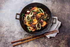荞麦混乱油炸物面条用海鲜-虾,章鱼,在生铁亚洲铁锅的乌贼有烹调的筷子 顶层 免版税图库摄影